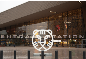 Image of outside ENTRA STATION with a large white Tiger Logo in front of the building in honour of the International Film Festival Rotterdam